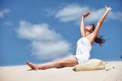 Het uitrekken van de vrouw zich op strand Stock Foto's