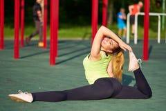 Het uitrekken van turnervrouw die spleet, streng in de grond van trainingsporten doen stock afbeelding