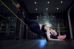 Het uitrekken van turnervrouw die verticale spleet, streng doen Zijaanzicht van aantrekkelijke jonge vrouw die kernoefening op ge royalty-vrije stock afbeelding