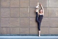 Het uitrekken van turnervrouw die verticale spleet, streng op bruine stedelijke muurachtergrond doen royalty-vrije stock foto
