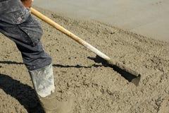 Het uitspreiden uit goot vers beton met een schop Stock Afbeeldingen