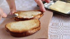 Het uitspreiden van boter op de toost stock videobeelden