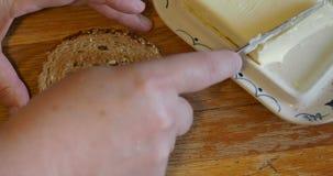 Het uitspreiden van boter op een boterham met mes