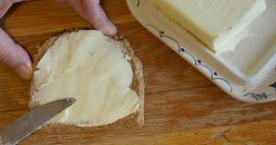 Het uitspreiden van boter op een plak van whole-grain brood