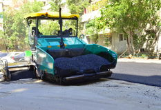 Het uitspreiden van het asfalt machine Het bedekken van de weg Stock Foto