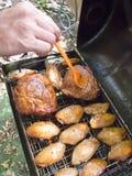 Het uitspreiden van Sausbbq op Varkensvleesschouder en Kippenvleugels stock fotografie
