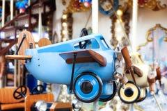 Het uitstekende blauwe vliegtuig van kinderen De carrousel van kinderen `s Jonge geitjesspeelgoed Weinig proef Retro vliegtuig ou stock afbeelding