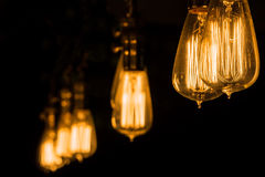 Het uitstekende Edison Light Bulbs-hangen tegen een zwarte achtergrond Stock Afbeelding