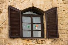Het uitstekende houten venster met shuttered in steenmuur stock afbeelding