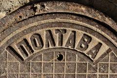 Het uitstekende mangat de USSR van het gietijzerriool maakte met de inschrijving POLTAVA in de stad van Dnipro, de Oekraïne, het  royalty-vrije stock afbeelding
