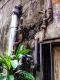Het uitstekende metaal door buizen leiden op een oud gebouw net boven venstertraliewerk stock foto's