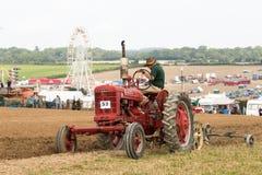 Het uitstekende rode farmalltractor ploegen stock foto