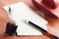 Het uitstekende rode vloeipapier van de leerinkt met retro prentbriefkaaren op leathe Stock Fotografie
