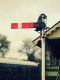 Het uitstekende signaal van het spoorwegeinde met seinhuisje en trein op de achtergrond Stock Fotografie
