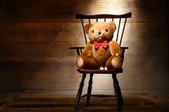 Het uitstekende Stuk speelgoed van de Teddybeer op Stoel in de Oude Zolder van het Huis Stock Afbeelding