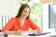 Het uitvoerende schrijven in een agenda en online het controleren Stock Foto's