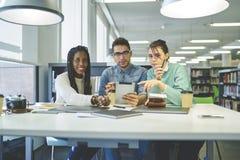 Het universitaire klasgenoten het samenwerken voorbereidingen treffen voor onderzoek in bibliotheek stock fotografie