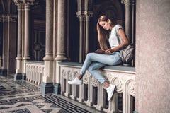 Het universitaire leven De jonge vrouwelijke studentenzitting op het traliewerk in de universitaire zaal en de lezing boeken royalty-vrije stock afbeelding