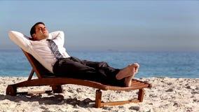 Het Unstressed zakenman ontspannen op het strand stock footage