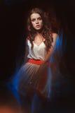 Het vage portret van de kleurenkunst van een meisje op een donkere achtergrond Maniervrouw met mooie make-up en een lichte de zom Stock Afbeelding