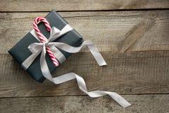 Het vakje van de Kerstmisgift in zwart document met suikergoedriet wordt verpakt op houten oppervlakte die Het in dozen doen dag, stock fotografie
