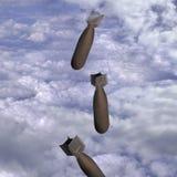 Het vallen van bommen door wolken stock foto's