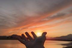 Het vangen van de zon met zijn hand bij zonsondergang Royalty-vrije Stock Foto's