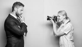Het vangen van het vertrouwen Zakenman het stellen voor vrouwelijke fotograaf Fotograaf die mannelijk model in studio schieten royalty-vrije stock afbeelding