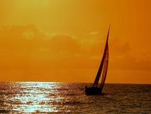 Het varen aan de zonsondergang Stock Afbeelding