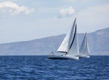 Het varen in de wind door de golven bij het Egeïsche Overzees in Griekenland Rijen van luxejachten bij jachthavendok royalty-vrije stock afbeelding