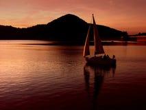 Het varen door de zonsondergang Stock Afbeeldingen