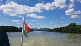 Het varen met een boot op een rivier met pluizige wolken op een zonnige de zomerdag