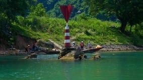 Het varen voorbij boei op rotsen door rivierbank en lange boot stock footage