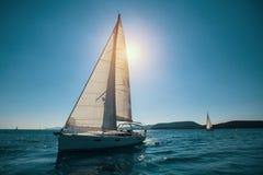 Het varende jacht van de schipluxe met witte zeilen in het Overzees Sport stock afbeeldingen
