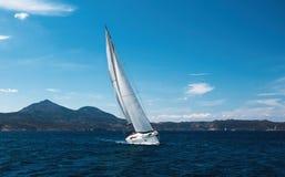 Het varende luxejacht met witte zeilen glijdt door de golven in het Overzees stock fotografie