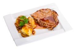 Het varkensvlees van het braadstuk met jus en aardappels Stock Afbeeldingen
