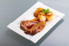 Het varkensvlees van het braadstuk met jus en aardappels Royalty-vrije Stock Foto