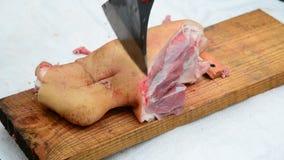 Het varkensvleesgewricht van slagers verkeerd besnoeiingen met een bijl stock footage