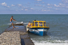 Het vastleggen van de boot aan een concrete golfbreker voor de inscheping of de ontscheping van passagiers van het strand in toev Stock Fotografie