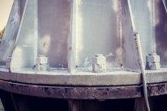 Het vastmaken van de bouten van de hoogspanningstoren aan de bodem stock foto