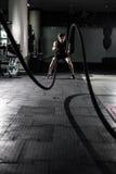 Het vechten van Crossfit kabels bij de oefening van de gymnastiektraining Crossfit stock afbeelding