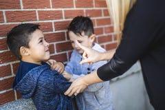 Het Vechten van leraarsstopping two boys in Speelplaats stock foto's