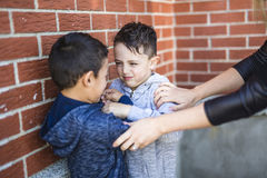 Het Vechten van leraarsstopping two boys in Speelplaats stock fotografie