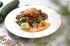Het vegetarische koken Kleurrijke plantaardige meatless schotel Gekookte linzen met wortelpuree en geroosterde courgette stock foto