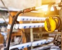 Het veiligheidslawaai op het werk, gele hoofdtelefoons tegen lawaai hangt in de workshop voor de vervaardiging van pvc-vensters stock afbeeldingen