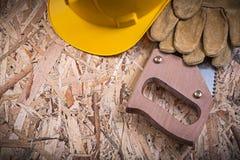 Het veiligheidsleer gloves de bouwhelm handsaw op spaanplaat Royalty-vrije Stock Foto's
