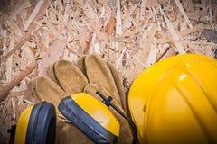Het veiligheidsleer gloves de oorbeschermers van de de bouwhelm op spaanplaat Royalty-vrije Stock Afbeeldingen