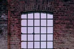 Het venster die in de bakstenen muur van een verlaten oud gebouw openen stock fotografie