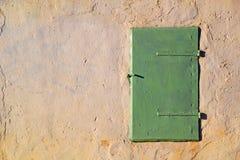 Het venster sloot groen blind op de muur stock foto