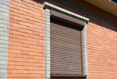 Het venster van het baksteenhuis met rollend blind voor huisbescherming royalty-vrije stock fotografie